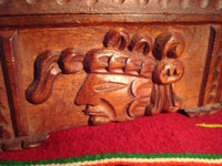 Mexican vintage wood-carving and Mexican vintage folk art, a wooden box beautifully carved with Mayan faces and designs, c. 1930-40. The top of the box bears a silver plaque with wonderful Mayan symbols or faces. Closeup of Mayan face on front of the box.