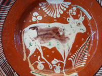 Mexican vintage pottery and ceramics, a bandera-ware charger with a wonderful bull, Tonala or Tlaquepaque, Jalisco, c. 1930's. The charger is decorated with the colors of the Mexican flag (bandera, in Spanish), white, green, and red. Closeup of the bull on the front of the charger.