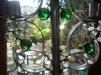 BU-3: Mexican vintage tinwork art, and Mexican vintage folk art, a lovely tinwork-art candlelabra with five green glass spheres as decorations, Oaxaca, c. 1940's. Closeup photo showing the glass spheres decorating the tinwork art candlelabra.