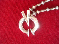 "Native American Indian vintage sterling silver jewelry, and Navajo silver jewelry, a wonderful sterling silver necklace with a ""V"" on the naja, symbolizing Victory in World War II, c. 1945. Closeup photo showing the naja with the ""V""."