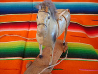 Mexican vintage folk art, a wonderful paper mache toy horse with wooden wheels, Mexico, 1937. Photo showing a frontal view of the horse's face.