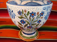 Mexican vintage pottery and ceramics, a spectacular pottery vase or urn with a cream-colored background, fantastic artwork, and covered with tiny stars, Tonala or San Pedro Tlaquepaque, c. 1920-30's.  Closeup photo of the floral designs near the base of the vase.