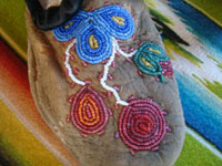 Native American Indian vintage beadwork, and vintage folk art, a beautiful pair of Cree child's mocassins with very fine and colorful beadwork, c. 1920's or earlier. Closeup of the front of one mocassin showing the very fine beadwork designs.