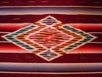 Mexican vintage textiles, a Saltillo sarape, c. 1940. Beautiful burgundy background. Made of very finely woven wool with silk in the center medallion and decorative side-bars.  Closeup of center medallion.