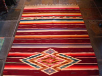 Mexican vintage textiles, a Saltillo sarape, c. 1940. Beautiful burgundy background. Made of very finely woven wool with silk in the center medallion and decorative side-bars.  A photo showing most of the saltillo.