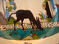 Mexican vintage pottery and ceramics, a lovely plate with a cream-colored background glaze and a wonderful and very serene scene of a burro munching grass under graceful trees and foliage, Tlaquepaque, Jalisco, c. 1930's.  Closeup photo of the burro.