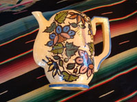 Mexican vintage pottery and ceramics, a beautiful coffee pot with a cream-colored background glaze and exquisite floral decorations, Tlaquepaque, Jalisco, c. 1940's. View of the side of the pot, lying down on one side.