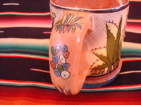 Mexican vintage pottery and ceramics, a set of four mugs with petatillo backgrounds and wonderful artwork, attributed to the famous artist, Balbino Lucano, Tlaquepaque, Jalisco, c. 1930. Photo showing the back of the handle of one mug with wonderful floral decorations.