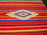 Mexican vintage textiles and Saltillo serapes (sarapes), a wonderful Saltillo serape with a red background and a beautiful center medallion, Saltillo, Coahuilla, c. 1940. Closeup photo of the lovely center medallion of the serape.