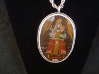 Mexican vintage devotional art, and Mexican vintage sterling silver jewelry, a beautiful relicario with the small retablo beautifully painted on tin, with a lovely sterling silver rope chain, c. 1920's.  Closeup photo of one side of the relicario.