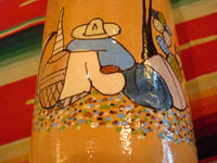 Mexican vintage pottery and ceramics, and Mexican vintage folk art, a pottery bottle from Tlaquepaque, Jalisco, c. 1930. The bottle has a lovely cream-colored background, with a wonderful scene of a snoozing Mexican campesino with his burro amidst wonderful trees and cacti. The artwork on this piece is exceptionally fine. A closeup photo of the snoozing campesino.