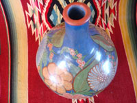 Mexican vintage pottery and ceramics, a wonderful burnished jar from Tonala, c. 1930's. The burnished jar is decorated with beautiful flowers, and has a wonderful blue background. Photo showing a view from above the jar.