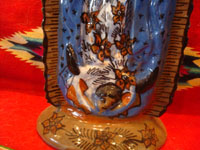 Mexican vintage devotional art, and Mexican vintage pottery and ceramics, a beautiful pottery figure of Our Lady of Guadalupe with wonderful form and colors, Tzintzuntzan, Michoacan, c. 1970.  Closeup photo of the bottom of the piece, showing the angel at Our Lady's feet.