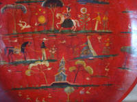Mexican vintage folk art, and Mexican vintage woodcarvings and masks, a beautiful wood-carved batea with a red laquer background and colonial designs, Michoacan, c. 1930's.  Closeup photo of the decorations painted on the front of the batea.