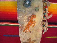 Native American Indian beadwork and folk art, a Plains knife-sheath with ghost-dance designs and symbolism, c. 1890-1910. The sheath is sinew sown with brain-tanned leather, and with fringe and bottom-tassles with beads. Closeup of beadwork horse on the front.