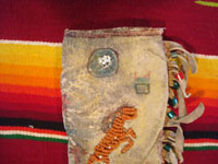 Native American Indian beadwork and folk art, a Plains knife-sheath with ghost-dance designs and symbolism, c. 1890-1910. The sheath is sinew sown with brain-tanned leather, and with fringe and bottom-tassles with beads. Closeup photo of the symbols near the top of the sheath.