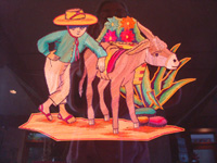Mexican vintage straw-art (popote art, or popotillo) and folk art, a straw-art picture of a campesino and his trusty burro, c. 1940's. The picture is composed of thousands of pieces of dyed and dried straw, popote in Spanish. Closeup photo of the man and his burro.