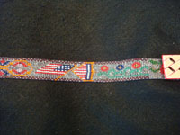 Native American Indian vintage folk-art and beadwork, a beautiful and very fine Lakota beadwork belt, with a lovely art-deco buckle, c. 1930's. The belt is beautifully beaded, with designs of American flags, whirling logs, and flowers. CLoseup photo of a part of the Lakota beadwork belt.