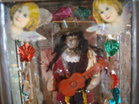 Mexican vintage tinwork art, and Mexican vintage devotional art, a beautiful tin and glass nicho with a statue of St. Fabian playing his guitar and with two lovely angels, Oaxaca, c. 1940's. Closeup photo of the saint's face.
