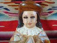 Mexican vintage devotional art, and Mexican vintage pottery and ceramics, a lovely chalk or plaster-art wall-hanging depicting the Santo Nino de Atocha, with glass eyes and with eye-lashes, c. 1940's. Closeup photo of the Nino's face.