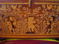 Mexican vintage folk art, and Mexican vintage woodcarvings and masks, a fabulous wooden escritorio (portable writing desk) with very fine marquetry inlay work, Oaxaca, c. 19th century. Closeup photo of the marquetry on the front cover of the desk, featuring human figures and floral designs.
