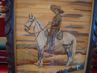 Mexican vintage straw-art (popote art or popotill0), a wonderful picture created with thousands of pieces of dyed straw or grass, featuring a Mexican gentleman (charro) mounted on his beautiful horse (perhaps a popote art portrait of the revolutionary war hero Emiliano Zapata), c. 1930's. Closeup photo of the straw-art picture (popote art or popotillo).