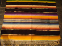 Mexican vintage textiles and Saltillo serapes (sarapes), a beautiful Saltillo serape (sarape), finely wovern, with silk in the center medallion and a very warm pumkin-colored background, c. 1940's.  Closeup of one end of the Saltillo sarape.