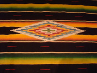 Mexican vintage textiles and Saltillo serapes (sarapes), a beautiful Saltillo serape (sarape), finely wovern, with silk in the center medallion and a very warm pumkin-colored background, c. 1940's.  Closeup photo of the lovely center medallion of the Saltillo sarape.
