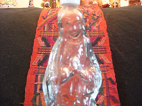 Mexican glassware, and Mexican devotional art, a very unique clear bottle in the form of Our Lady of Guadalupe, c. 1940's. These bottles were used to bring Holy Water home from church. Closeup photo of Our Lady's face.
