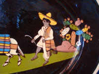 Mexican vintage pottery and ceramics, a black-ware, oval charger with exquisite and very endearing artwork, Tlaquepaque or Tonala, Jalisco, c. 1930's. Closeup photo of the wonderful Mexican campesino behind his trusty burros.