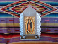 New Mexican vintage devotional art, and New Mexican vintage folk art. a wonderful retablo depicting Our Lady of Guadalupe, done on hand-adzed wood with a surrounding stamped tinwork-art frame, New Mexico, c. 1990. Main photo of the New Mexican retablo by Madrid.