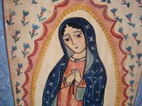 New Mexican vintage devotional art, and New Mexican vintage folk art. a wonderful retablo depicting Our Lady of Guadalupe, done on hand-adzed wood with a surrounding stamped tinwork-art frame, New Mexico, c. 1990. Closeup photo of the face of Our Lady of Guadalupe by the Madrid's.