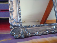 Mexican vintage tinwork art, and Mexican vintage folk art, a lovely mirror with a beautiful repousee silver frame, c. 1940's. Closeup photo of one corner of the silver repousee frame.