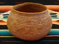 "J-2: Native American Indian basket, Mission bowl with rattlesnake, c. 1920. Sumac with natural gold juncus in the rattlesnake design, which begins with the tail and rattles on the bottom of the basket and winds to the head of the rattlesnake on the side of the basket. 4"" tall x 7"" wide at middle x 4 3/4"" diameter at mouth. Price: $2750."