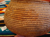 Photo of the side of the Mission Indian basket showing the contiuation of the rattlesnake design ending with the head and fangs.