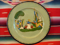 I-12: Mexican vintage pottery and ceramics, a Tlaquepaque plate with pale green background and wonderful hand-painted artwork and a beautiful squiggle pattern around the outer edge, c. 1930.