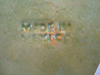 A closup photo showing the signature stamped onto the back of the vintage Mexican pottery plate from Tlaquepaque.