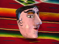 Mexican vintage wood carving and Mexican vintage folk art, a dance mask depicting a European woman, from Guerrero, c. 1930-40. View of the side of the mask.