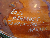 Mexican vintage pottery and folk art, a lovely petatillo casserole with lid, Tonala, Jalisco, c. 1950-60, by famed artist Jose Bernabe. The casserole features wonderful and very intricate floral and zoomorphic figures. Photo of the bottom of the casserole with Barnabe's signature.