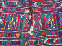 Guatemalan vintage clothing, and Guatemalan vintage textiles and huipiles, a lovely huipil of hand-woven cotton with intricate and colorful designs and decoration, San Juan Zacatepequez, Guatemala, c. 1950's.  Closeup photo of the front of the vintage Guatemalan blouse or huipil, showing the cluster of coins decorating the front.