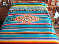 Mexican vintage textiles, and Mexican vintage Saltillo sarapes (serapes), a beautiful Saltillo-style sarape with a lovely turquoise background and a woncerful center medallion and decorative sidebars, c. 1930's. Another photo of the sarape covering a full-size bed.