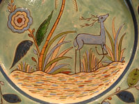 Mexican vintage pottery and ceramics, a beautiful Tlaquepaque pottery plate with a soft teal-colored background and with fine artwork decorations, featuring a lovely, graceful deer, Tonala or Tlaquepaque, c. 1930's. Closeup photo of the graceful deer.