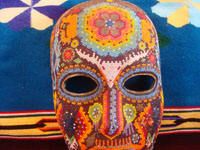 CI-13: Mexican vintage woodcarvings and masks, a beautiful beaded Huichol mask with very intricate and crisp design elements, the Sierras of Nyarite, c. 1950's. Closeup photo of the top part of the mask, showing the peyote bud on the front above the eye-openings.
