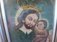 Mexican and New Mexican vintage devotional art, a New Mexican tin retablo painted with the images of St. Joseph and the Child Jesus, New Mexico, c. 1930's. Closeup photo of the faces of St. Joseph and the Child Jesus.