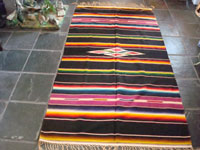 Mexican vintage textile, a Saltillo Sarape, c. 1940. Wonderfully woven of fine wool with silk in the center diamond and decorative side-bars.