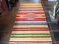 Mexican vintage textile, a Saltillo sarape, c. 1920. Woven of very fine wool with silk in the center diamond and side-bar decorations.  This is another photo of the entire Saltillo sarape.