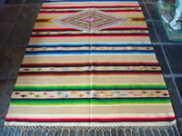 Mexican vintage textile, a Saltillo sarape, c. 1920. Woven of very fine wool with silk in the center diamond and side-bar decorations.  A closeup photo of the Saltillo sarape.