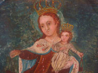 Mexican vintage devotional art and folk art, a retablo on tin depicting Our Lady of Mt. Carmel of the Scapulars, holding the Infant Jesus wearing his crown, c. 1900. Closeup photo of Our Lady's face.