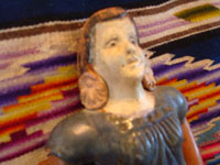 Mexican vintage pottery and ceramics and Mexican vintage folk-art, a wonderful bank in the form of a lovely Mexican woman, c. 1940's. The woman's face is very serene and beautiful, and the doll-bank has great patina. Closeup of the woman's face.
