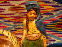Mexican vintage pottery and ceramics and Mexican vintage folk-art, a lovely pottery figurine depicting a lovely woman with a basketl, Tonala or Tlaquepaque, Jalisco, c. 1930's. The woman's face is incredibly beautiful. Closeup of the maiden's face.